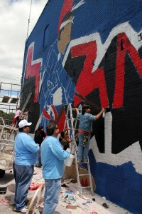 Osage youth helped artists with NVision paint a mural on the side of the Osage language building in downtown Pawhuska May 14. Photo by Shannon Shaw/Osage News